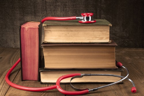 Old Books on Wood Table With Red Stethoscope